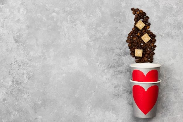 Concetto amore per il caffè. bicchieri di carta grigia per bevande con cuore rosso, chicchi di caffè su uno sfondo chiaro. vista dall'alto, copia spazio. sfondo di cibo