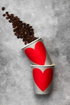 Concetto amore per il caffè. bicchieri di carta grigia per bevande con cuore rosso, chicchi di caffè su uno sfondo chiaro. vista dall'alto. sfondo di cibo.