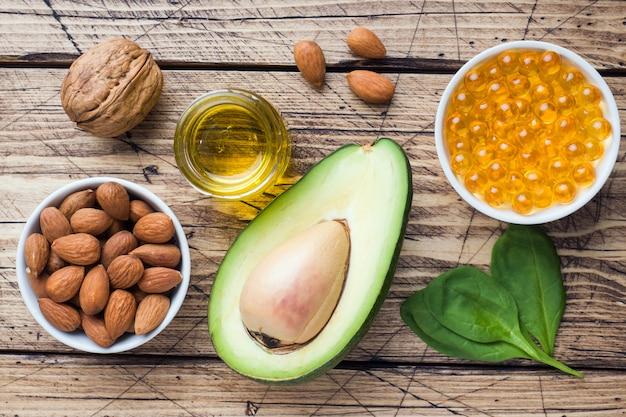 Concetto antiossidante prodotti alimentari sani avocado, noci e olio di pesce, pompelmo su fondo in legno.