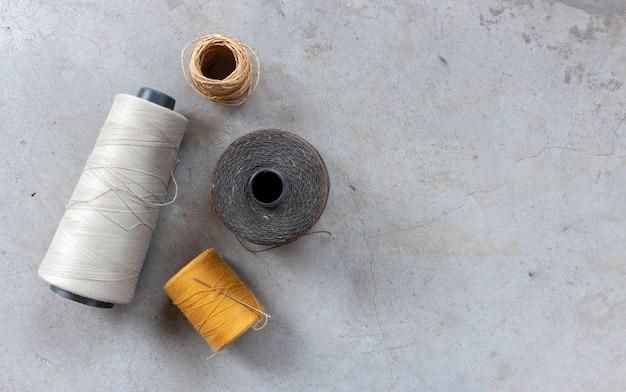 Concetto artigianale e fai-da-te. fili per cucire sul pavimento di cemento. vista dall'alto