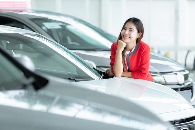 Concetto asiatico della commessa, di affari automatici, di vendita dell'automobile, di gesto e della gente - donna di affari felice.