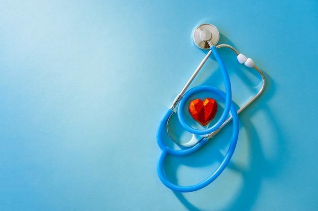 Concetto astratto di giornata mondiale della salute con lo stetoscopio e lo spazio rosso della copia del cuore. assistenza sanitaria.