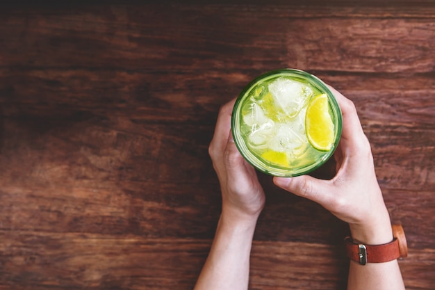 Concetto bevente femminile della limonata del ghiaccio. rilassarsi con un bicchiere di caipirinha o succo di limone tropicale