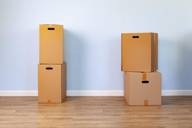 Concetto commovente della casa con le scatole di cartone impilate in una stanza