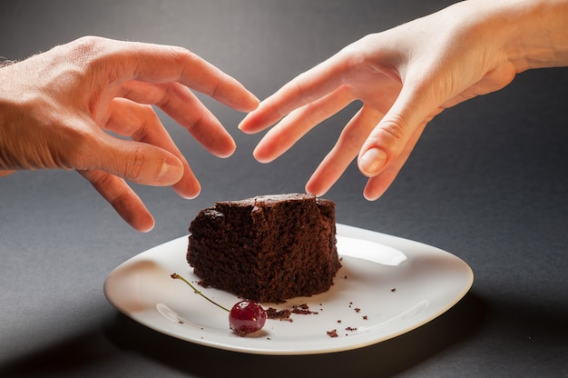 Concetto con le mani e la torta al cioccolato