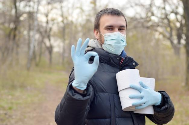 Concetto covidiot. il giovane nella maschera protettiva tiene molti rotoli di carta igienica e mostra il gesto giusto all'aperto in legno di primavera