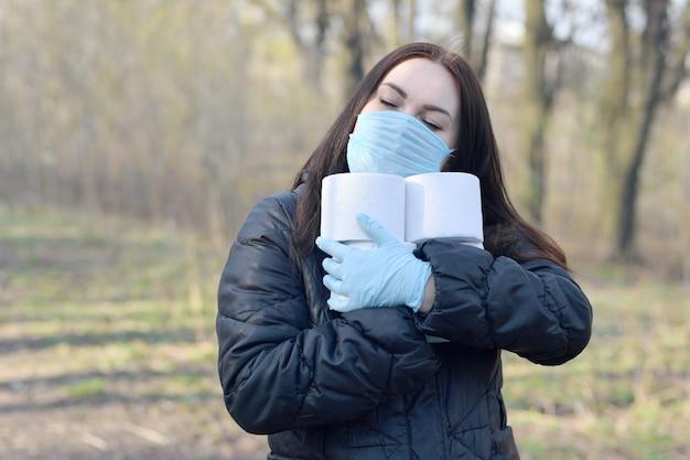 Concetto covidiot. la giovane donna nella maschera protettiva tiene molti rotoli di carta igienica all'aperto nel legno di primavera