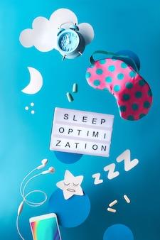 Concetto creativo di sonno di notte sana con il ceppo di sonno o il taccuino del diario. oggetti volanti o levitanti: maschera per dormire, sveglia, smartphone, auricolari, tappi per le orecchie e pillole. stella di carta, zzz, luna, nuvole.
