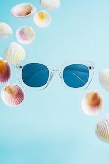 Concetto creativo estivo. stile minimal con occhiali da sole e conchiglie trasparenti