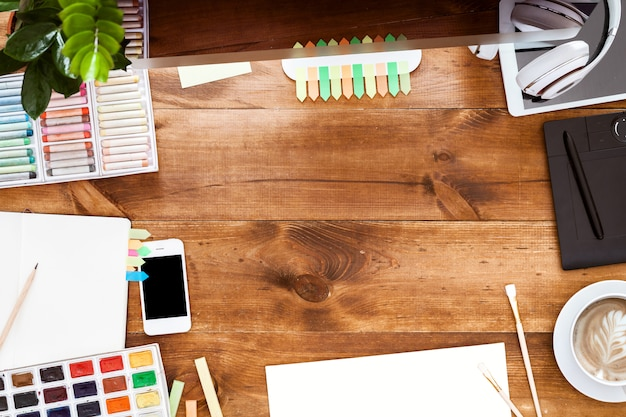 Concetto creativo moderno del worktable di progettazione, pitture del computer sulla tavola di legno marrone
