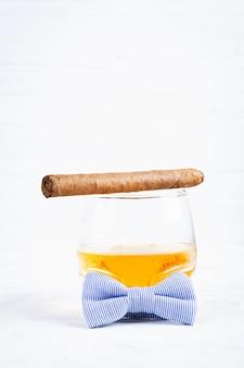 Concetto d'annata con la vista di whiskey e del sigaro su fondo bianco