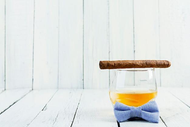 Concetto d'annata con la vista di whiskey e del sigaro su fondo di legno bianco
