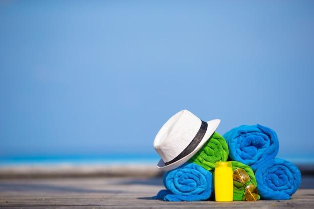 Concetto degli accessori di vacanze estive e della spiaggia - primo piano degli asciugamani, del cappello e della protezione solare variopinti