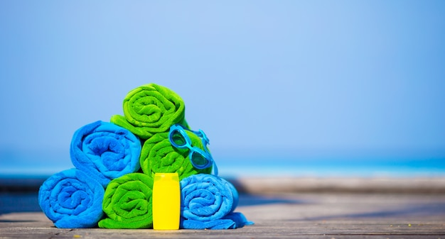 Concetto degli accessori di vacanze estive e della spiaggia - primo piano degli asciugamani variopinti, degli occhiali di protezione di nuoto e della protezione solare