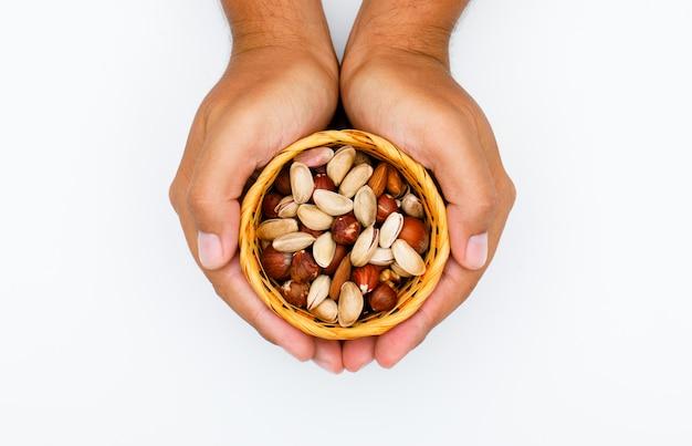 Concetto degli alimenti sani sulla disposizione piana del fondo bianco. mani che tengono il piatto con noci miste.