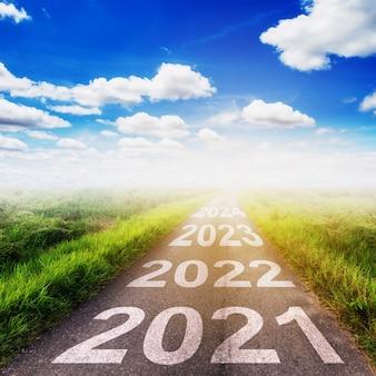 Concetto degli obiettivi del nuovo anno: tramonto vuoto della strada asfaltata e buon anno 2021.