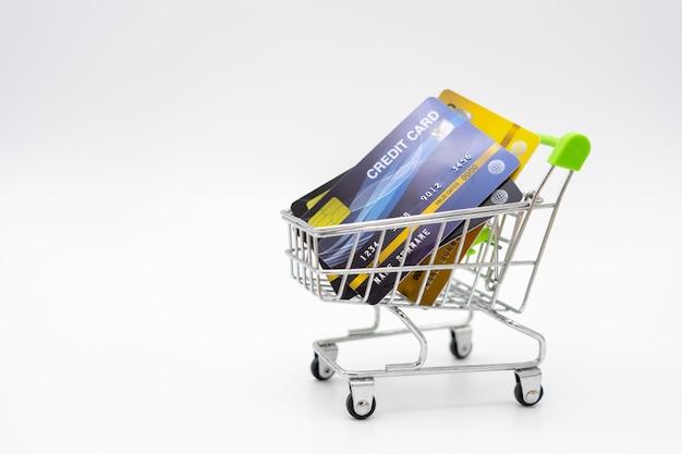 Concetto dei soldi delle carte di credito in un carrello sul bianco dell'isolato