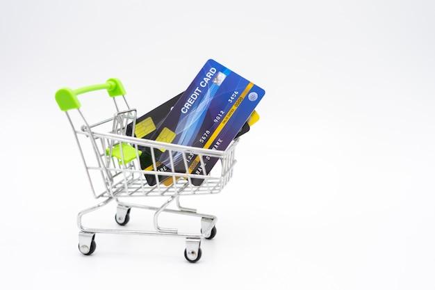 Concetto dei soldi delle carte di credito in un carrello sul fondo di bianco dell'isolato.