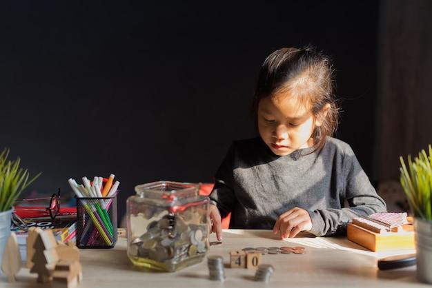 Concetto dei soldi di risparmio, giovane bambina che esamina le monete nella bottiglia, nella casa e nella penna