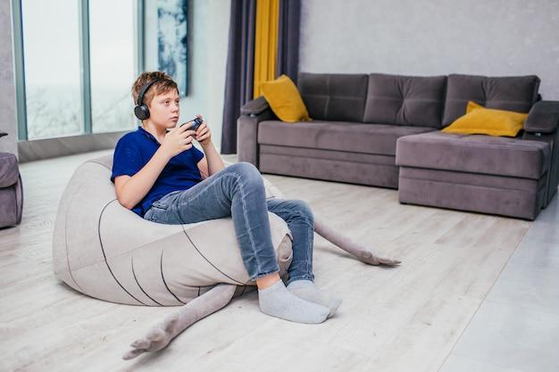 Concetto dei videogiochi di gioco - adolescente che gioca gioco con la leva di comando e le cuffie, godente della seduta sulla sedia molle in salone