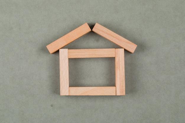 Concetto del bene immobile con i blocchi di legno sulla disposizione piana del fondo grigio.