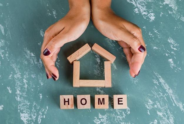 Concetto del bene immobile con la disposizione piana dei blocchi di legno. mani che racchiudono il modello di casa.