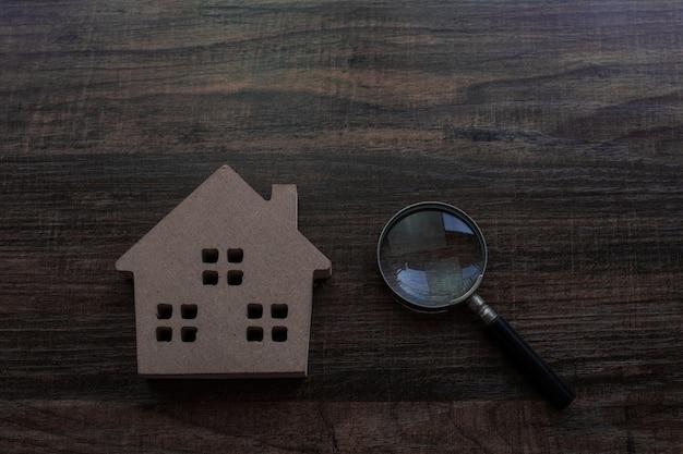 Concetto del bene immobile e dell'ispettore, modello della casa e lente d'ingrandimento sulla tavola di legno
