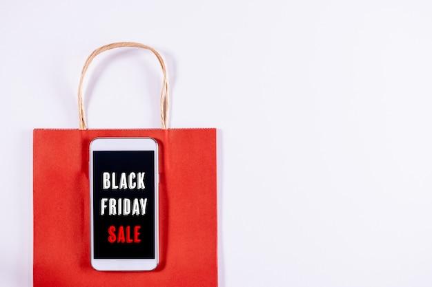 Concetto del black friday. telefono cellulare o smartphone con il sacco di carta rosso su fondo bianco.