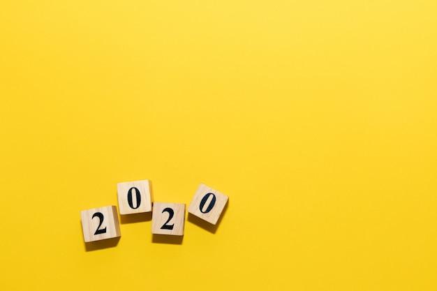 Concetto del buon anno 2020 con il cubo del blocco di legno su giallo