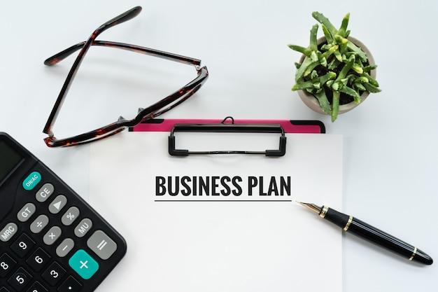 Concetto del business plan, appunti con piano aziendale di parola, penna, occhiali e calcolatrice
