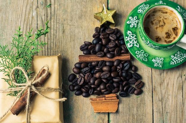 Concetto del caffè di natale con la tazza di caffè e i fagioli