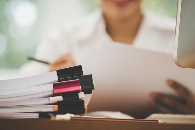Concetto del file di rapporto del bilancio di pianificazione di contabilità: gli uffici della donna di affari controllano il lavoro per organizzare