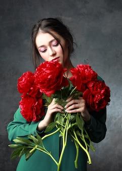 Concetto del giorno delle donne e della gente internazionale - la giovane donna asiatica felice con il mazzo di peonia fiorisce sopra fondo grigio