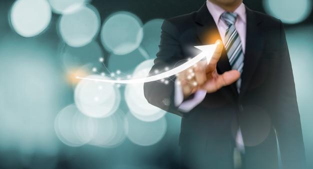 Concetto del grafico e della freccia indicante dell'uomo d'affari