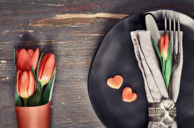 Concetto del menu di primavera con i tulipani freschi e la decorazione del cuore su legno scuro