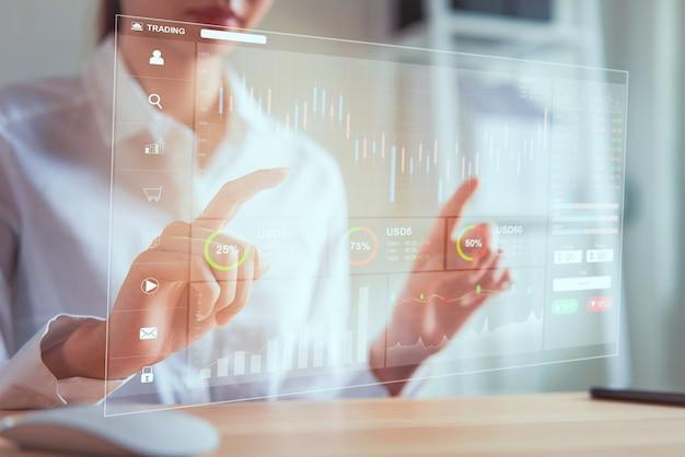 Concetto del mercato di borsa, commerciante della donna di affari che guarda la linea della candela di analisi dei grafici nella stanza dell'ufficio, diagrammi sullo schermo.