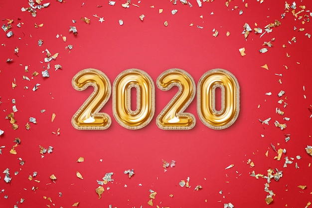 Concetto del nuovo anno 2020 - cartolina d'auguri festiva rossa con coriandoli e lettere