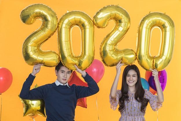 Concetto del nuovo anno 2020. il ritratto di bella giovane donna asiatica sorridente e l'uomo astuto che tengono il pallone dorato di numero e il pallone del colorfull fanno festa