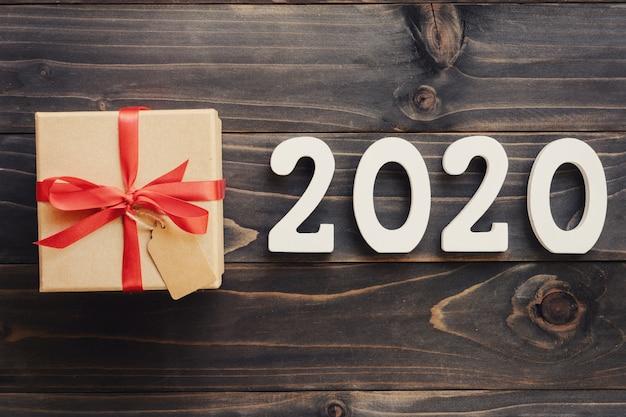 Concetto del nuovo anno 2020: numero di legno 2020 e confezione regalo marrone su sfondo di tavolo in legno.