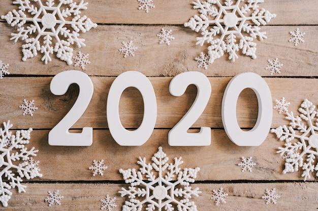 Concetto del nuovo anno 2020 sulla tavola di legno e sul fondo della decorazione di natale.