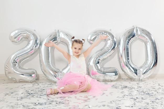 Concetto del nuovo anno, di feste e di celebrazione - la bambina che si siede vicino con i palloni di numeri 2020