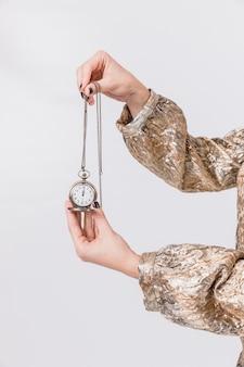 Concetto del partito del nuovo anno con l'orologio della tenuta della ragazza