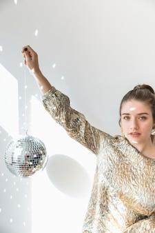 Concetto del partito del nuovo anno con la palla della discoteca della tenuta della ragazza