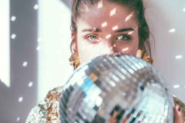 Concetto del partito del nuovo anno con la ragazza dietro la palla della discoteca