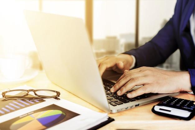 Concetto del piano di contabilità di affari, lavorando al computer portatile da tavolino con il calcolatore per la fabbricazione dell'affare, mano dell'uomo di affari che funziona con il computer portatile sul consulente di investimento aziendale dello scrittorio di legno.
