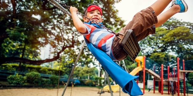 Concetto del ragazzo del bambino di libertà del supereroe del cortile del campo da giuoco
