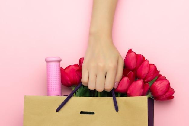 Concetto del regalo con vino e tulipani rossi nel sacco di carta sui precedenti rosa. disteso, copia spazio. la mano della donna tiene un presente al giorno delle donne, il giorno di madri, concetto della molla. decorazione floreale