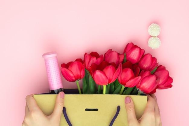 Concetto del regalo con vino e tulipani rossi nel sacco di carta sui precedenti rosa. disteso, copia spazio. le mani della donna tengono un presente al giorno delle donne, il giorno di madri, concetto della molla. decorazione floreale