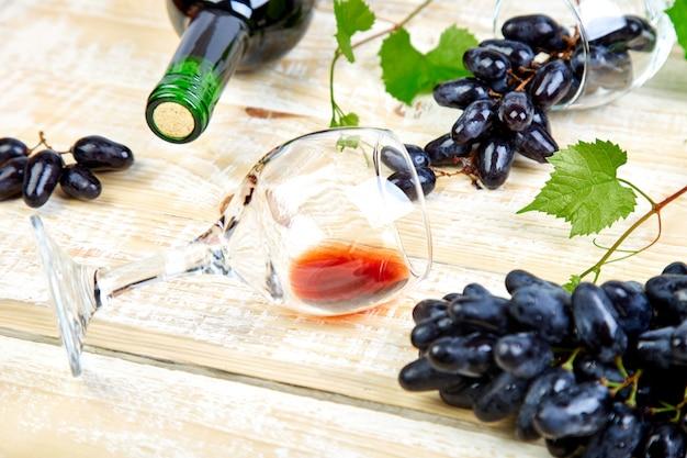 Concetto del vino rosso con la bottiglia, il vetro e l'uva