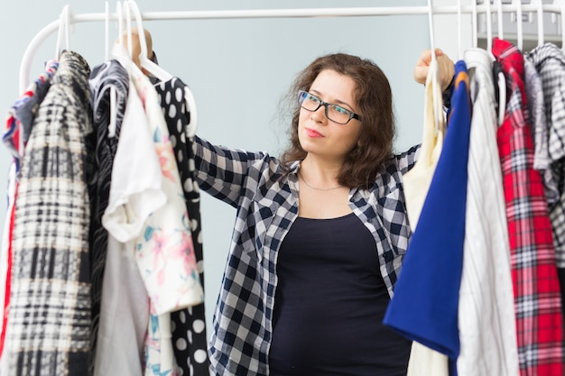 Concetto dell'abbigliamento, di modo, di stile e della gente - donna che sceglie il guardaroba dei vestiti a casa